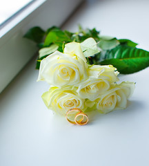 Bouquet of white roses and wedding rings