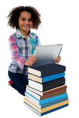 Smiling child busy with tablet pc and books