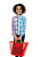 Happy school girl carrying stationery in basket