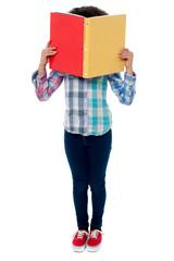 School girl hiding her face with a book