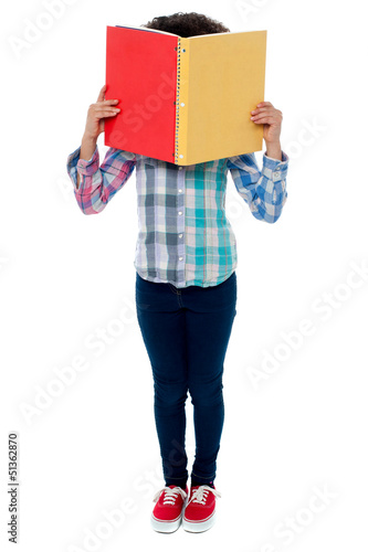 School girl hiding her face with a book