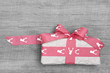 Weihnachtsgeschenk mit roter Schleife auf Holz