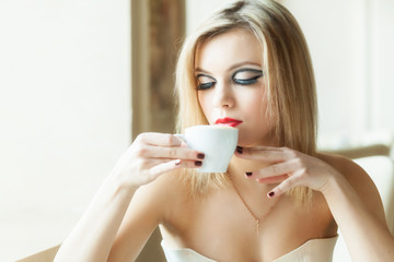 A woman in the restaurant is drinking coffee
