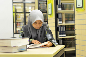 Young Muslim student studying in the library