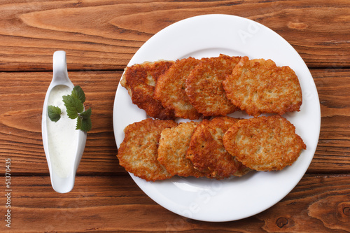Potato pancakes with sour cream sauce top view