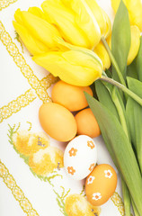 Yellow tulips and colored eggs on the embroidered cloth