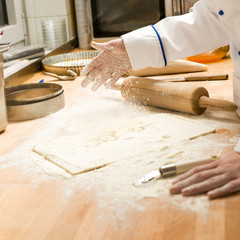 Chef pouring flour dough and rolling pin