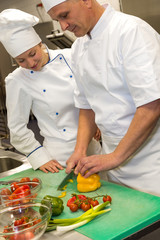Apprentice learning cutting vegetables from chef