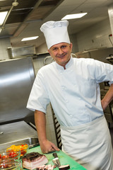 Male chef posing in commercial kitchen
