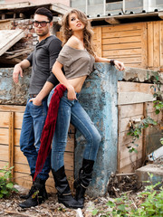 attractive fashionable couple wearing jeans posing dramatic