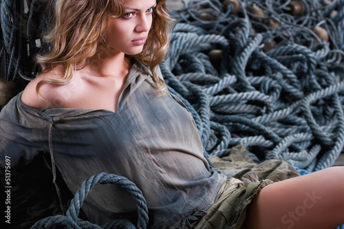 sexy pirate woman standing on ropes - fashion shoot
