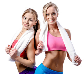 Two beautiful girls after workout with towels isolated on white