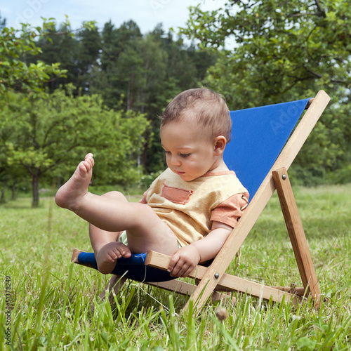 Baby on deckchair in garden