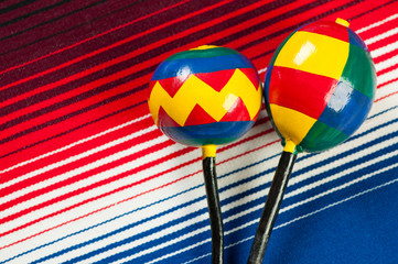 Mexican multi-colored wooden maracas and poncho, view from above