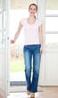 Attraktive Frau geht durch Haustür