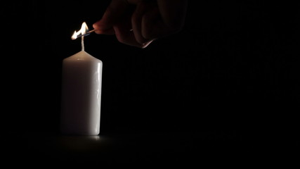 Simple white candle on black background.