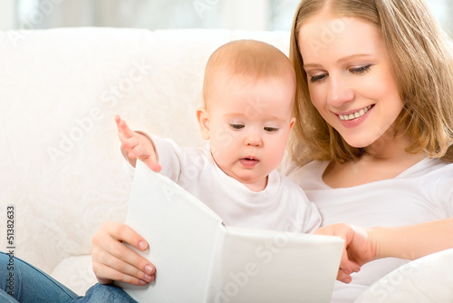 Mother reading a book a little baby on the sofa