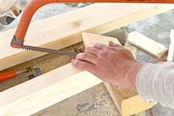 Closeup of hand cutting wood with a hand saw