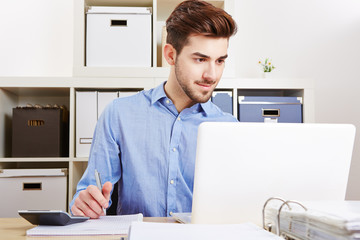 Junger Geschäftsmann arbeitet am Laptop im Büro