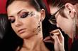 Brunette having applied face tattoo by makeup artist