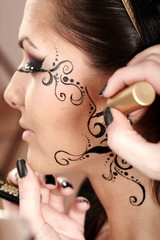 Brunette having applied face tattoo by makeup artist