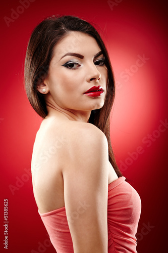 Beautiful brunette posing on red background