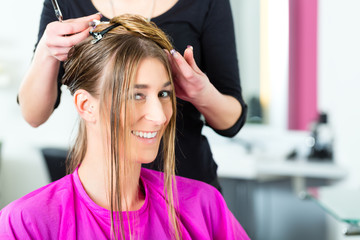 Woman receiving haircut from hair stylist or hairdresser