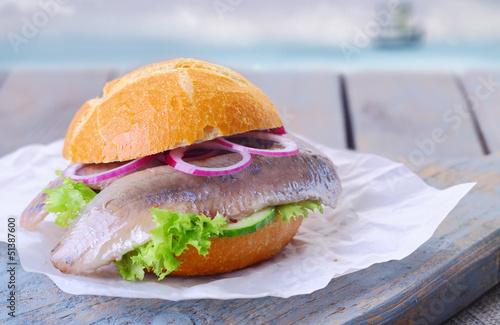 Matjesbrötchen auf einem Teller vor der Nordsee - 51387600