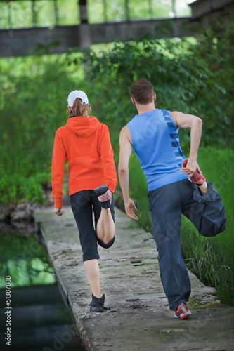Caucasian couple warming up before running training