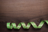 green measuring tape over brown wooden background