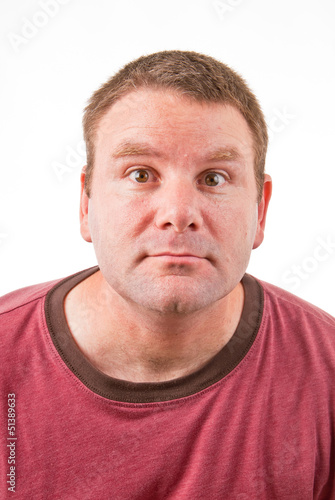 A clean shaven Caucasian leaning forward making a funny face