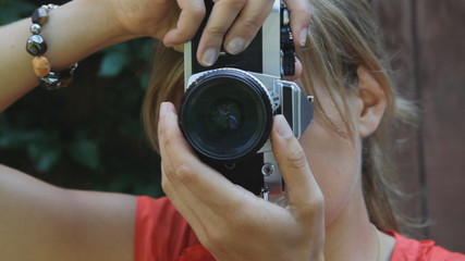 Young woman takes a photograph with 35mm film camera.