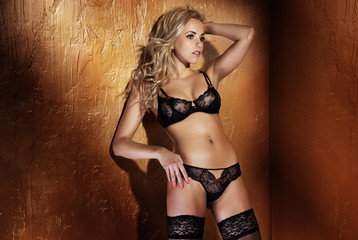 Beautiful blonde lady wearing black sexy lingerie posing.
