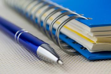 Spiral blue notebook and pen