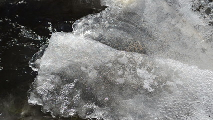 ice covering rapid water flow stream air bubbles form winter