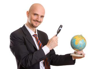 Mann schaut mit Lupe auf Globus