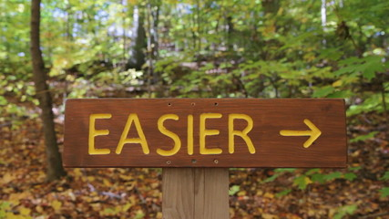 Easier and Harder signs on Mountain Bike trails. Two shots.
