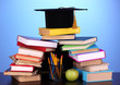 Books and magister cap against school board