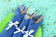 Forks and knives wrapped in blue paper napkins,