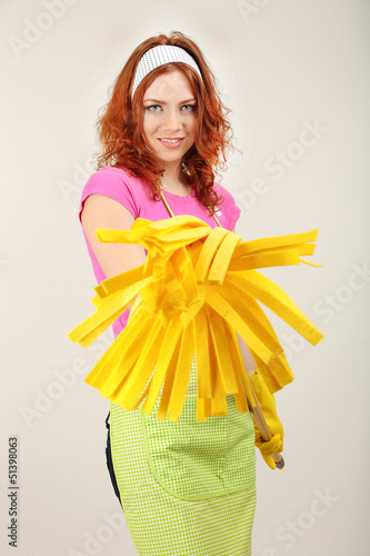 Young housewife with mop on grey background