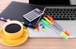 Laptop with stationery and cup of coffee on table