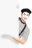 Smiling male mime artist showing on a panel
