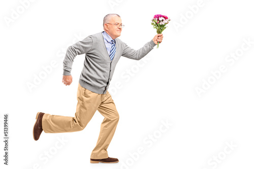 Full length portrait of a mature gentleman running with flowers