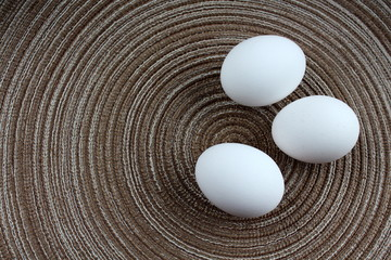 Three white eggs on brown textured mat