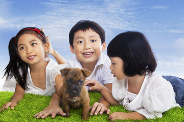 Children play with dog puppy