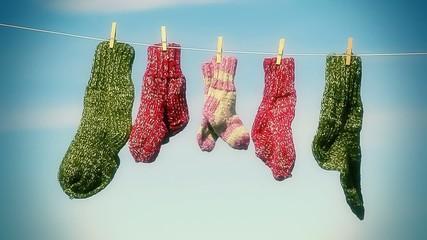 Three pairs of woolen socks hanging on rope