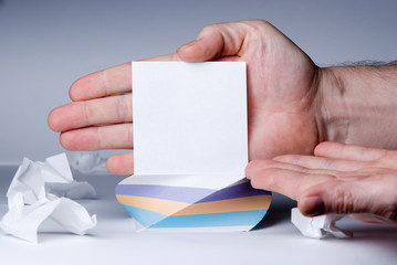 Men's hand points to a blank sheet of paper for notes