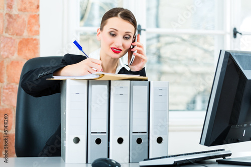 businesswoman in office makes notes in a file