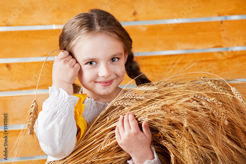 Beautiful girl holding ears of wheat