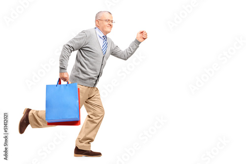 Full length portrait of a smiling gentleman running with shoppin